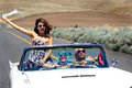 Party girls in convertible three attractive pretty riding a with the top down out on a desolate country road shallow depth of Stock Photography