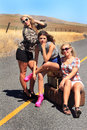 Party girls hitch hiking three sexy wearing short shorts and high heels are with their luggage on a remote desolate country road Royalty Free Stock Photos