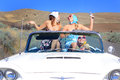 Party girls live it up three attractive pretty living riding in a classic convertible with the top down on a desolate country road Royalty Free Stock Images