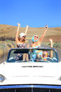 Party girls ride three attractive pretty riding in a classic convertible with the top down on a desolate country road smoking Royalty Free Stock Photography