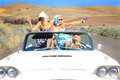 Party girls three attractive pretty riding in a classic convertible with the top down on a desolate country road smoking Royalty Free Stock Images