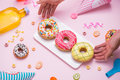 Party. Hand holding plate of colourful sugary round glazed donut Royalty Free Stock Photo