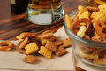 Party mix as a bar snack bowl of treats with beer in the background Stock Photo