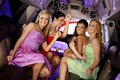 Party time in limousine attractive girls evening dress having limo smiling Stock Photos