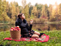 Partying haughty woman with a basket of apples on a picnic Stock Photos