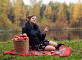 Partying haughty woman with a basket of apples on a picnic Stock Photo