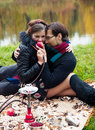 Partying relationship between men and a women at a picnic with a hookah Stock Photo