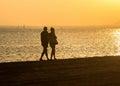 Paseo romántico a lo largo de la playa en los pares de la puesta del sol Imagenes de archivo