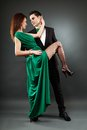 Pasionate young couple dancing tango over grey background elegant and passionate romantic in full length pose Royalty Free Stock Photography