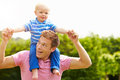 Passeio de giving young son do pai em seus ombros no jardim Fotografia de Stock Royalty Free