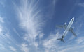Passenger aircraft flying in blue sky Stock Photos
