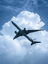 Passenger airplane flying in the sky processed in blue large strange concept of cautious traveling Stock Image
