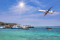 Passenger airplane landing above tropical sea with cruising ships and boats moored in bay. Royalty Free Stock Photo