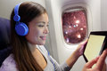 Passenger in airplane using tablet computer woman plane cabin smart device listening to music on headphones Stock Images