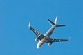 Passenger plane in a clean blue sky, bottom view. Royalty Free Stock Photo