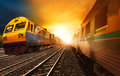 Passenger trains and industry container railroads running on ra railways track against beautiful sun set sky use for land Stock Photo