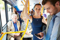 Passengers standing on busy commuter bus using mobile phone device Royalty Free Stock Image