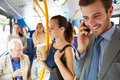 Passengers standing on busy commuter bus using mobile phone smiling Royalty Free Stock Images