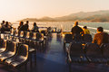 Passengers watching the sea from a ferry at sunset Stock Photography
