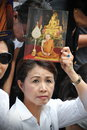 Passing of the thai sumpreme patriarch a roadside mourner holds a portrait supreme somdet phra nyanasamvara as a convoy carries Royalty Free Stock Images