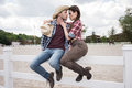 Passionate cowboy style couple kissing while sitting on fence at ranch Royalty Free Stock Photo