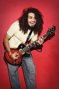 Passionate guitarist laughing with joy long curly hair playing g Royalty Free Stock Photo