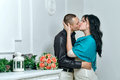 Passionate kiss of young couple near bouquet of roses Stock Photography