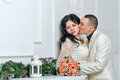 Passionate kiss of young couple near bouquet of roses Stock Images