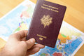 Passport in hand with a world's maps in background Royalty Free Stock Photo