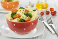 Pasta with broccoli and cherry tomatoes in a bowl on a wooden table Royalty Free Stock Images