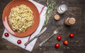 Pasta carbonara with zucchini, in a brown plate with vintage knife and fork, with herbs and spices on rustic wooden background top Royalty Free Stock Photo