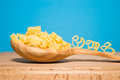 Pasta in the form of animals and a spoon on a blue background wooden Royalty Free Stock Image