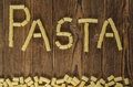 Pasta inscription made with macaroni on wood background Royalty Free Stock Photo
