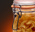 Pasta jar closeup of a full of on a light to dark warm background Royalty Free Stock Image