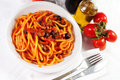 Pasta olives bacon sauce table wine oil tomatoes Stock Photo