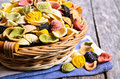Pasta orecchiette in a wicker basket on a wooden surface Stock Photo