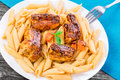 Pasta penne with appetizing grilled ribs with carrots and basil on an white dish on old wooden table, close-up Royalty Free Stock Photo
