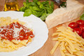 Pasta penne tomatoe sauce and ingredienses on a table Royalty Free Stock Photo