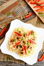 Pasta on a plate, fork and knife on old wooden background, chopped red pepper and green onions on a cutting board. Top view Royalty Free Stock Photo