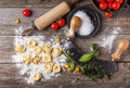 Pasta ravioli on flour top view homemade old wooden table with basil tomatoes and vintage kitchen accessories Stock Images