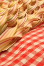 Pasta ribbons and gingham cloth photo of colourful strips of with serrated edges resting on a country kitchen red tablecloth Stock Photography