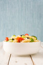 Pasta salad in a bowl on white wooden background Royalty Free Stock Photo
