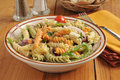 Pasta salad mediterranean with a small basket of dinner rolls Stock Photos