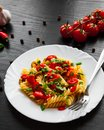 Pasta salad with tomato and olive in plate on dark wooden background Royalty Free Stock Photo