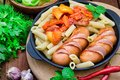 Pasta with sausages and lecho. Wooden rustic background. Selective focus. Top view Royalty Free Stock Photo
