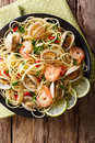 Pasta spaghetti with clam, shrimp, chili and lime close-up. Vert Royalty Free Stock Photo