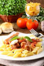Pasta with tomato sausage and ricotta on complex background Stock Photos