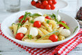 Pasta with vegetables and slices of mozzarella cheese in a plate on napkin italian food Stock Photos