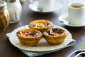 Pasteis de nata and espresso in cafe a plate a with three portuguese custard tarts on it the background are two cups of shakers Royalty Free Stock Photography