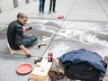 Pastel artist draws charlie chaplin on concrete plaza at beaubourg paris sits drawing huge greyscale portrait of red tip plates Royalty Free Stock Images